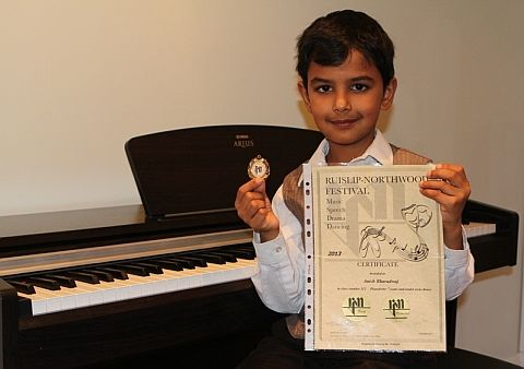 Image of piano student in Pinner with piano certificates